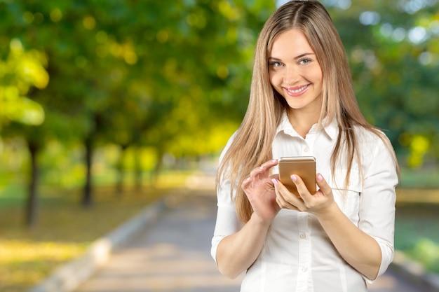 Счастливая коммерсантка стоя в ее офисе и используя телефон