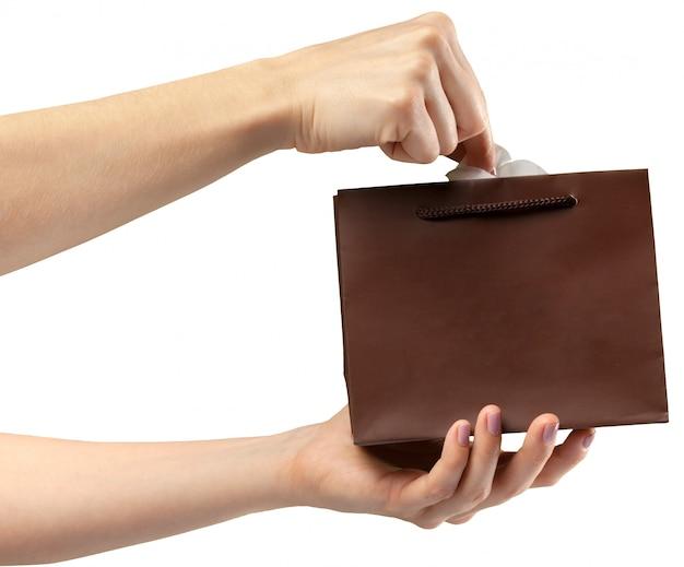 Сумка для покупок. женская рука держит сумку на белом