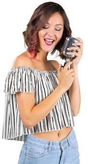 Молодая девушка с микрофоном поет