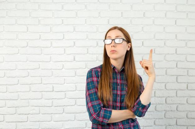若い女性のアイデア、指で上向き