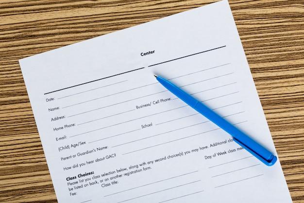 Ручка и контрактные документы на деревянный стол
