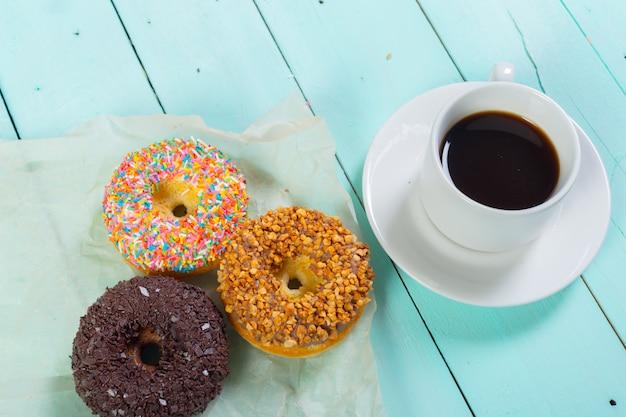 Пончики и кофе на деревянный стол. вид сверху