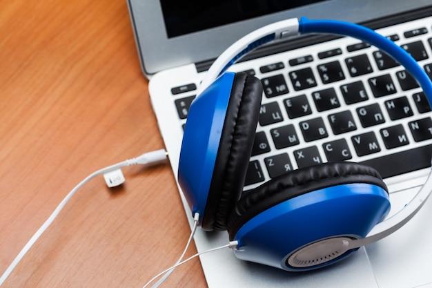 Наушники с ноутбуком на столе крупным планом