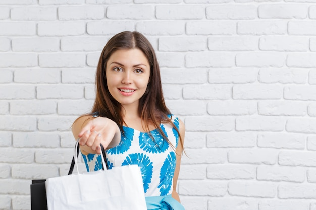 買い物袋を持つ若い幸せな笑顔の女性の肖像画