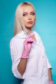 Красивый доктор молодой женщины в медицинской форме держа шприц