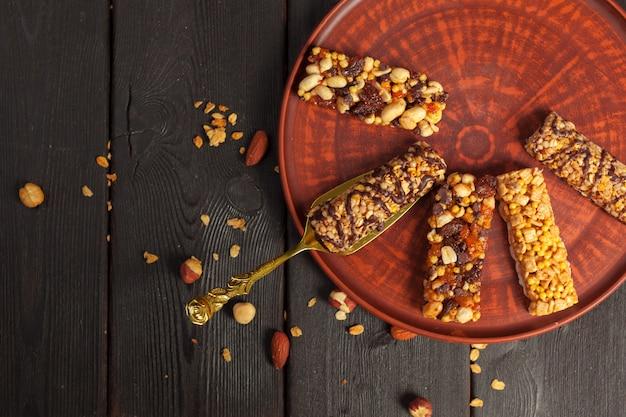 Здоровые батончики с орехами, семечками и сухофруктами на деревянном столе