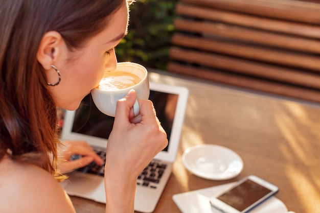 コーヒーブレーク中にラップトップを使用して女性