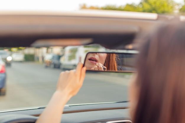 都市の晴れた日にコンバーチブルカブリオ車で美しい少女