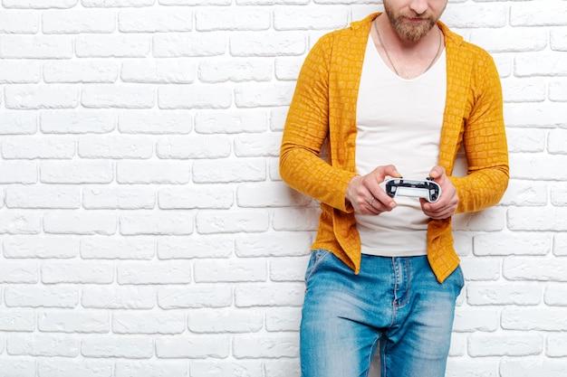 Молодой человек держит игровой контроллер, играя в видеоигры