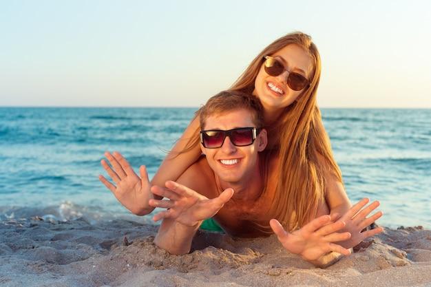 ビーチで楽しんでサングラスで幸せなカップル