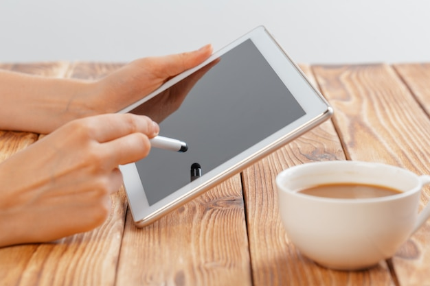 デジタルタブレットを押しながら朝マキアートを飲む若い女性の手のクローズアップ