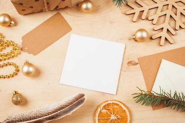 クリスマスの飾りに囲まれた挨拶状、封筒、羽