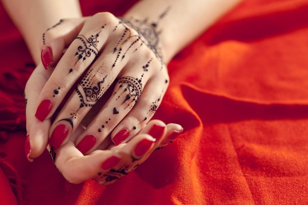 一時的な刺青の赤い手入れされた手