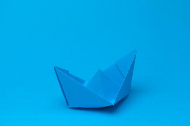 Оригами бумажный кораблик на синем