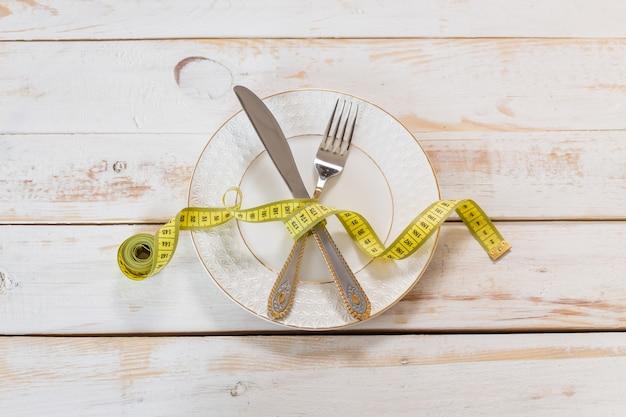 木製の背景に測定テープ。ダイエットのコンセプト