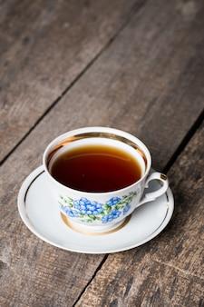 Крупным планом чашки чая на старинных деревянных фоне