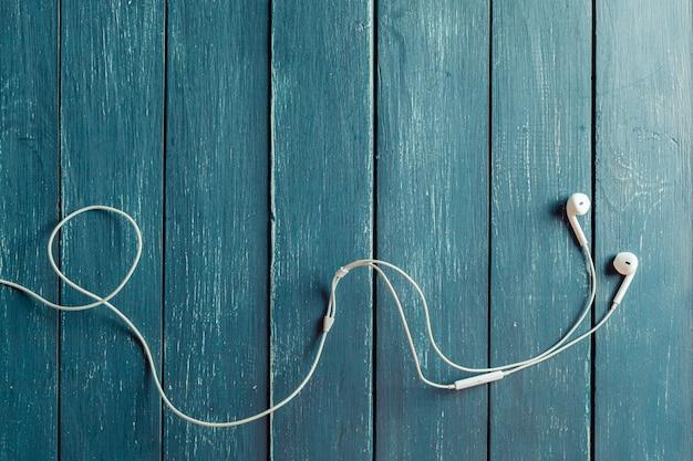 木板上の近代的なポータブルオーディオイヤホン
