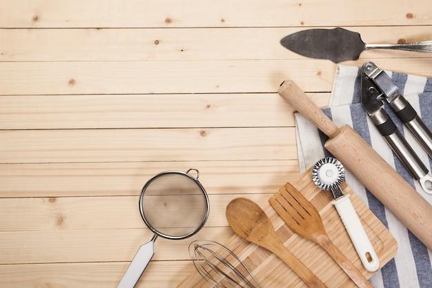 木製のスプーンやキッチンテーブルの上の青いナプキンと他の調理器具。