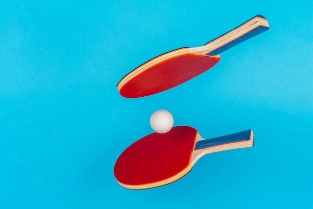 青色の背景に赤のピンポンラケット