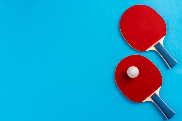卓球ラケットと青の背景にボール