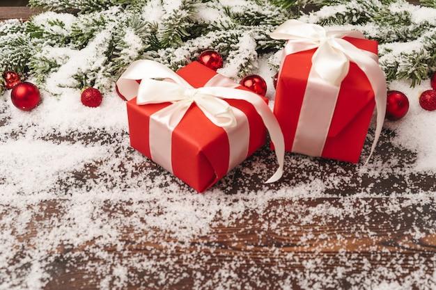 モミの木の枝と雪で粉にされた赤いつまらない木製の背景にプレゼント