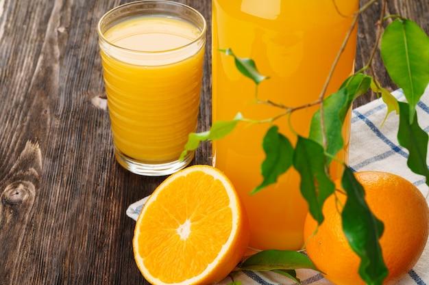 木製テーブルの上のオレンジジュースのガラスをクローズアップ