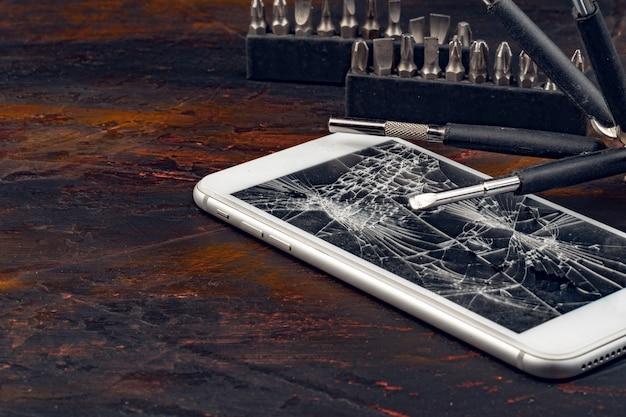スマートフォン修理コンセプト。スマートフォンとツールの破損したディスプレイ