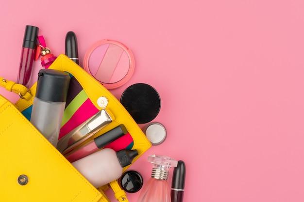 明るいピンクの背景に化粧品の完全な女性の小さなハンドバッグ