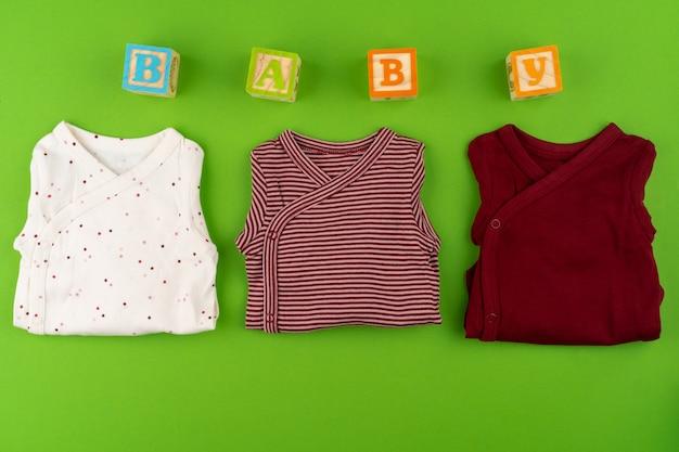 Вид сверху детской одежды на зеленом фоне