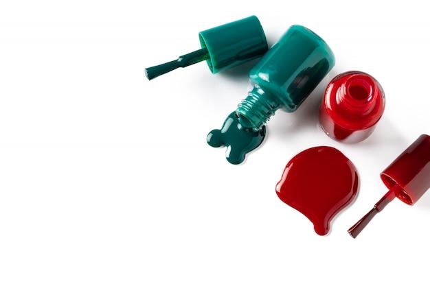 Лаки для ногтей, разлитые из бутылок на белом фоне