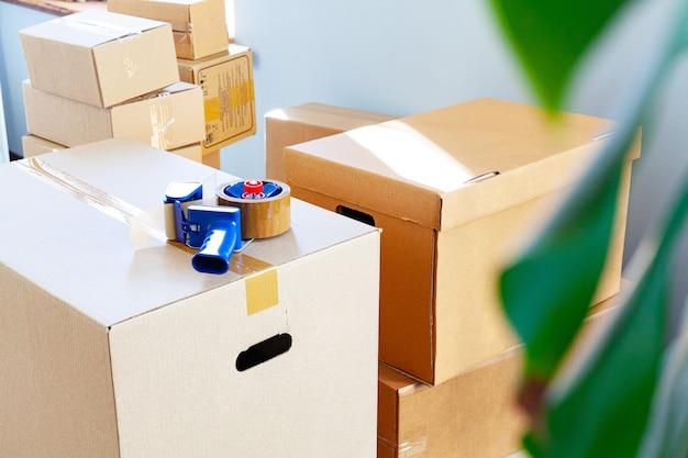 Концепция перемещения дома с сложенными картонными коробками в комнате