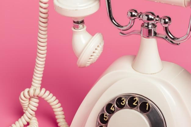 Ретро белый телефон на розовом фоне
