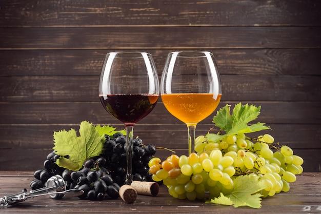 ワイングラスと木製のテーブルにブドウの房