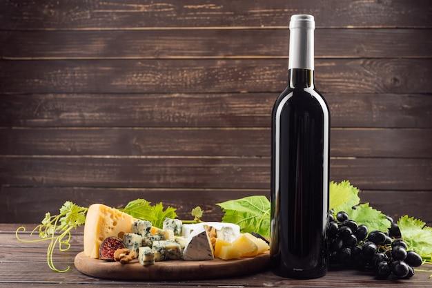 ワインのボトルと木製のテーブルのブドウ