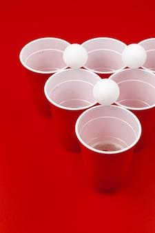 カップと赤の背景にプラスチックボール。ビールポンゲーム