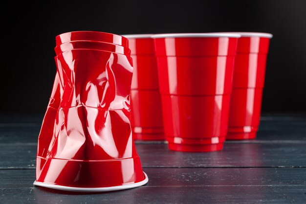 Деревянный стол с красными чашками и шариком для пинг-понга