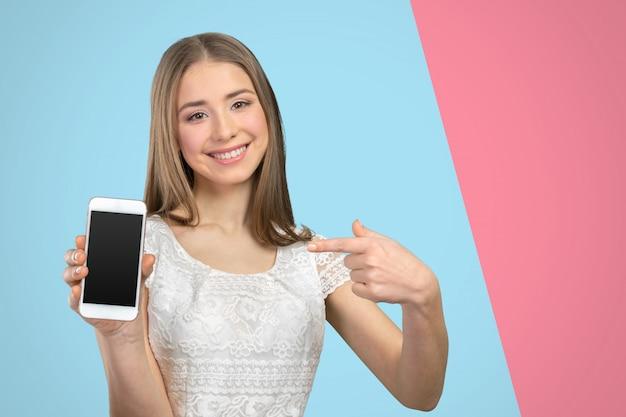 Счастливая милая женщина показывая пустой экран умного телефона