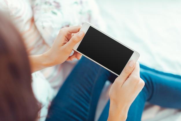 手で現代の携帯電話を持つ女性