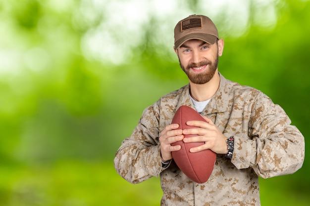 アメリカの兵士がサッカーボールを保持