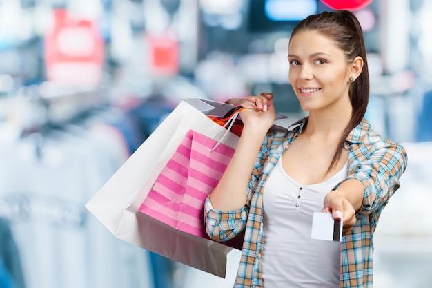 Улыбается молодая женщина с сумками