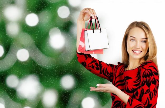 Кавказская счастливая молодая женщина с хозяйственными сумками