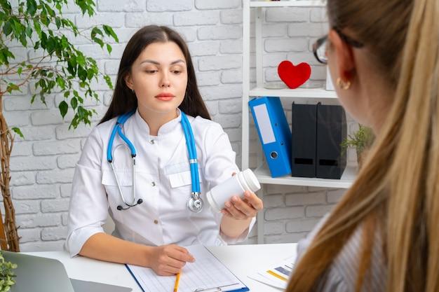 病院で患者に薬を処方する女医