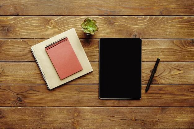 Цифровая таблетка с черным экраном и блокнотом и ручкой на деревянном столе