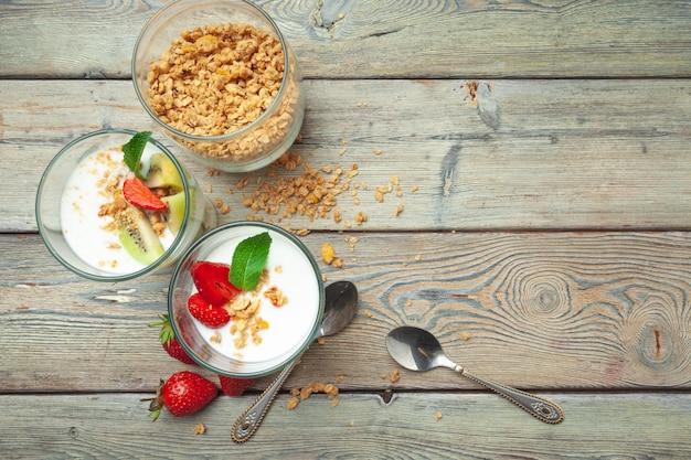 Здоровый завтрак с йогуртом, ягодами и мюсли на вид сверху деревянный стол