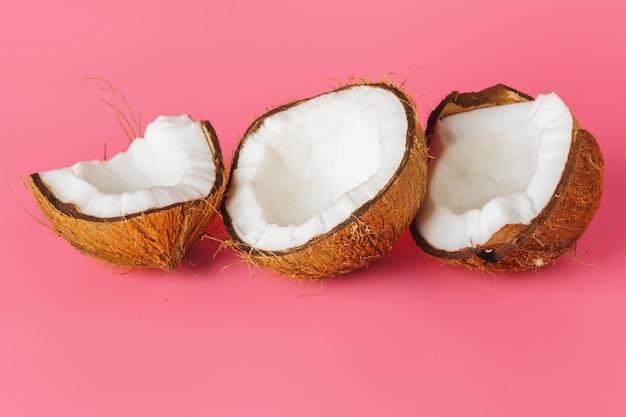明るいピンクの背景に半分のココナッツ
