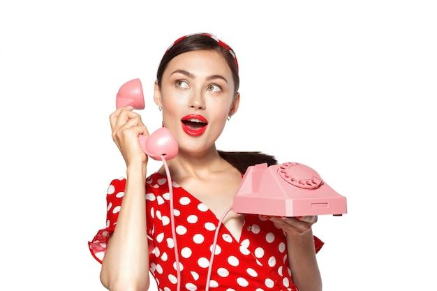 Портрет красивой молодой женщины с телефоном, одетый в стиле пин ап.