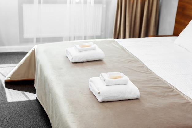 Белое полотенце на кровати в комнате для гостей отеля