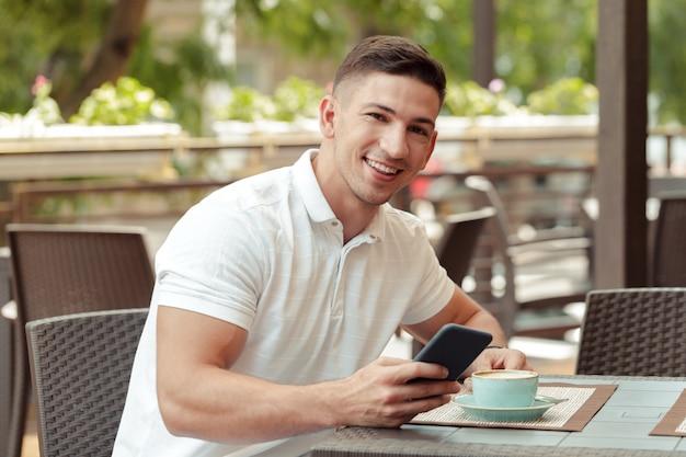 カフェでスマートフォンを使用して若い男