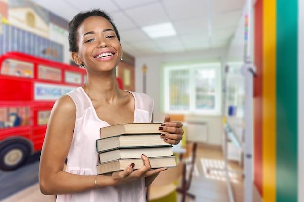 Афро-американских женщина, держащая кучу книг