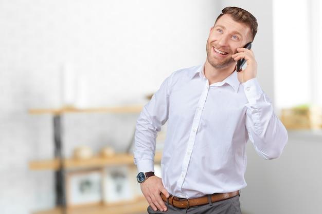 携帯電話で話しているハンサムなセールスマン